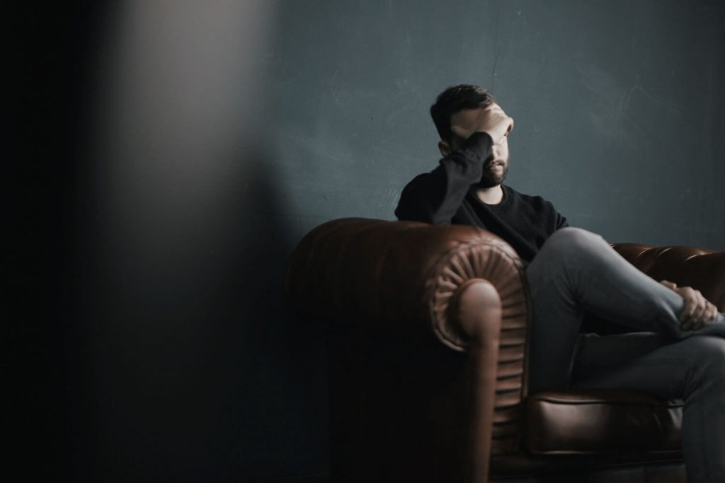Image of a man sitting on a couch. Side effects of Cannabidiol.