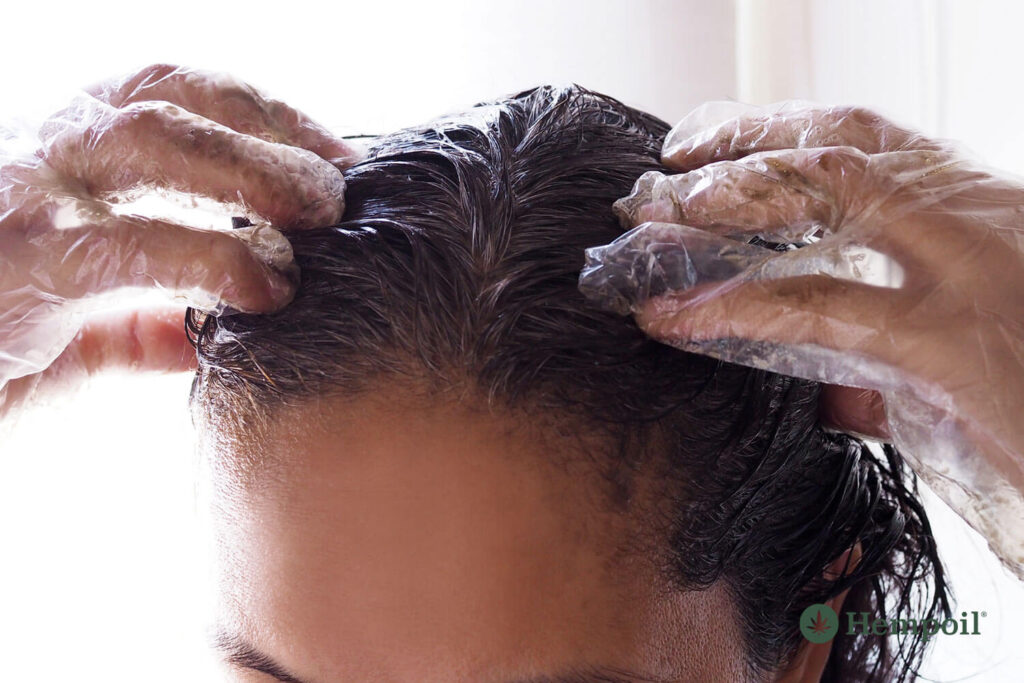 Woman applies a recipe with hemp oil and virgin olive oil to her hair.