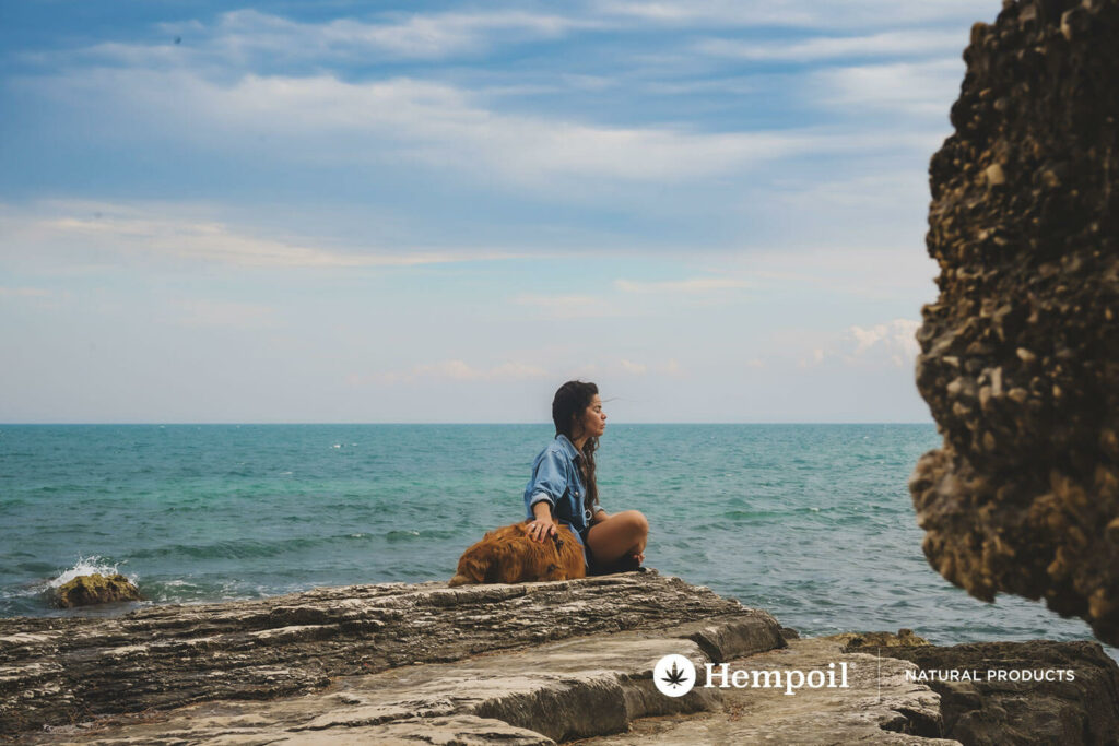 A dog and a woman relaxing by the sea during summer vacation