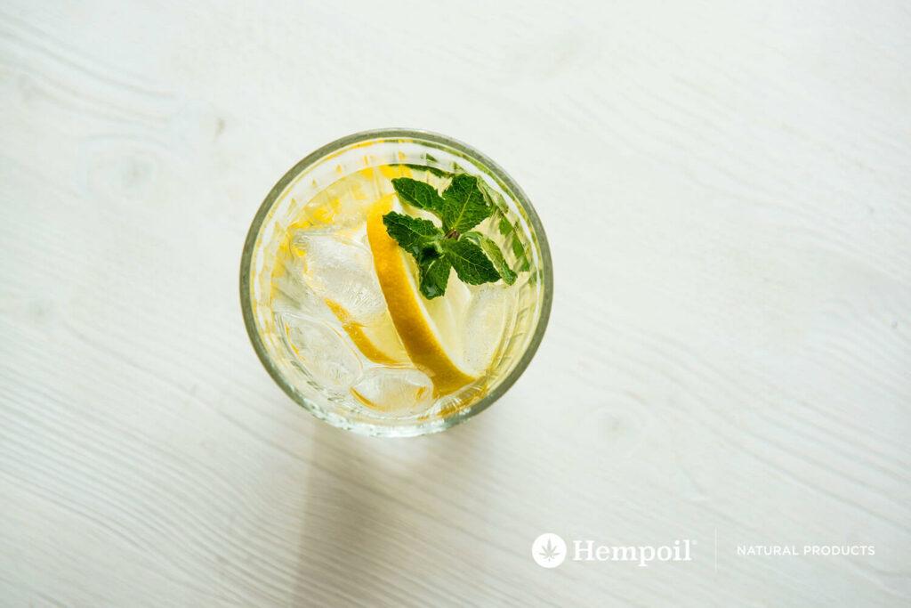 Ποτήρι με νερό, παγάκια, λεμόνι, βότανα και σταγόνες κάνναβης.